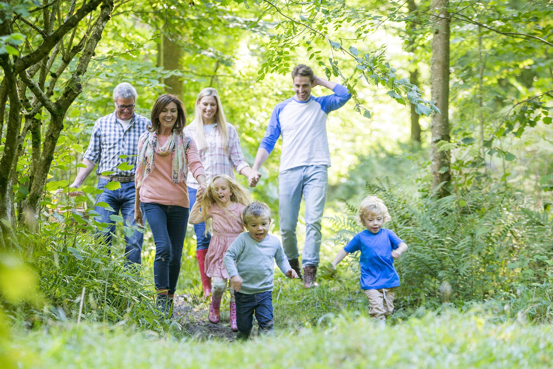 Photo d'une famille avec senior, parents et enfants se baladant en forêt pour illustrer l'importance du capital santé pour la famille »