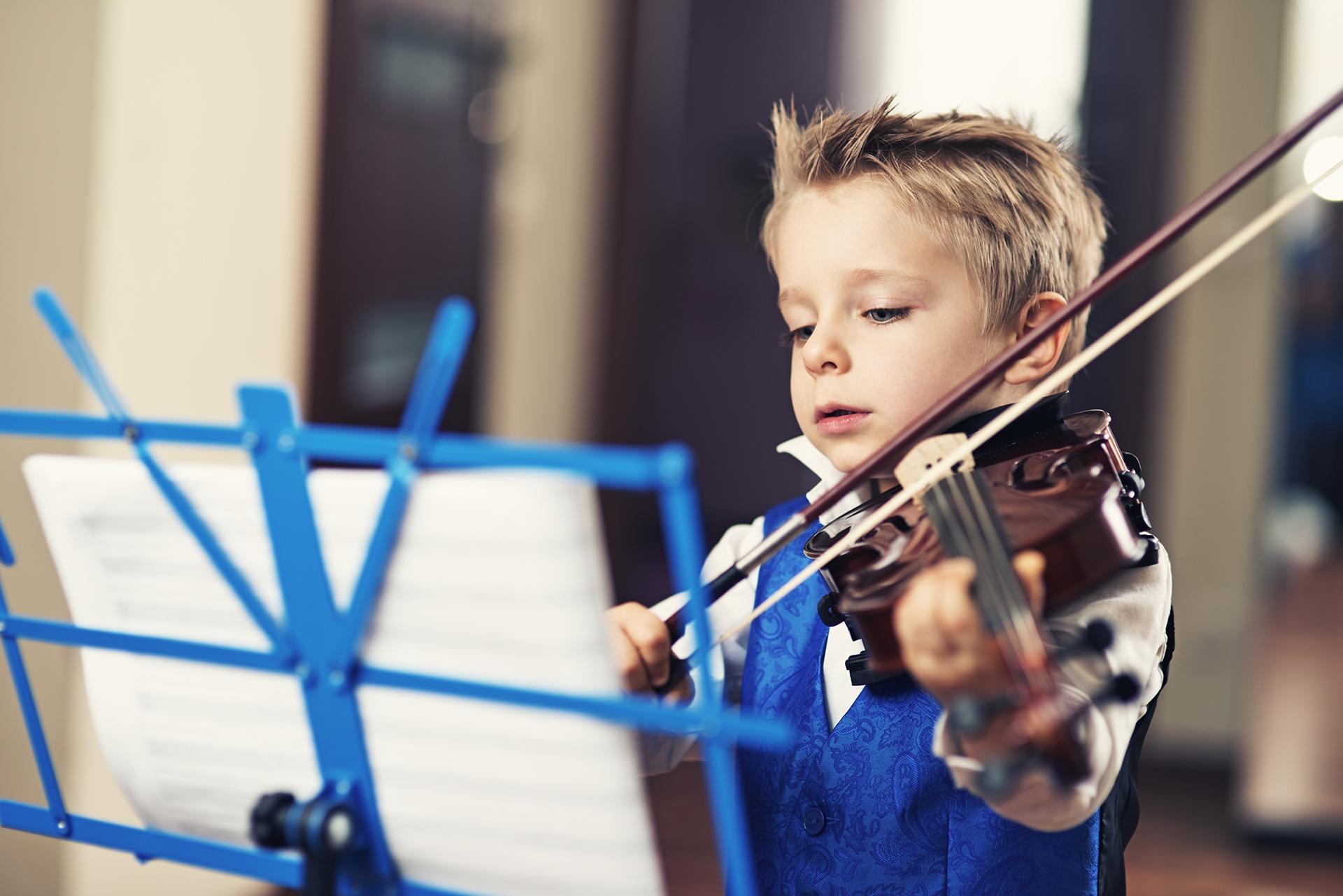 Jeune enfant jouant de la musique avec un violon pour illustrer la méthode neurofeedback, entrainement du cerveau en écoutant de la musique »