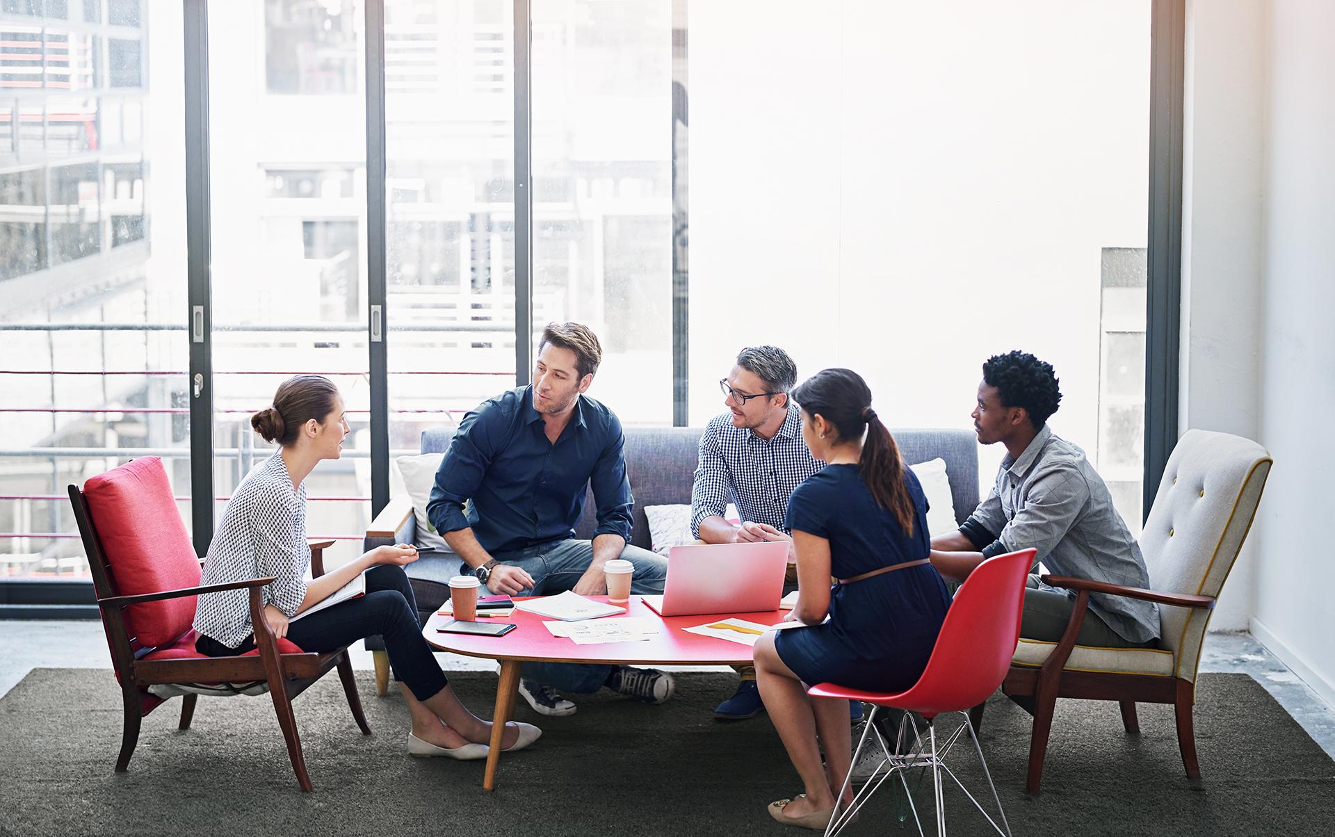 Dans une entreprise une équipe concentrée de 5 adultes actifs qui communiquent sans stress, l'institut neurofeedback normandie coach les professionnels